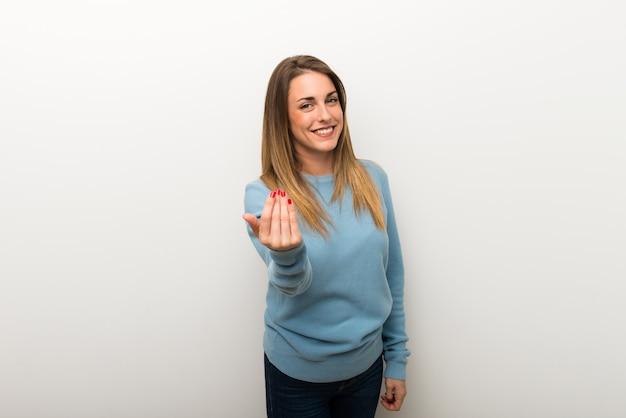 手で来ることを勧めている孤立した白い背景の上の金髪の女性。あなたが来たことを幸せに Premium写真