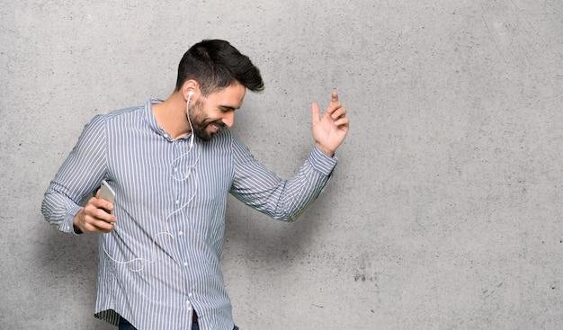 Элегантный мужчина в рубашке слушает музыку с телефона на текстурированной стене Premium Фотографии