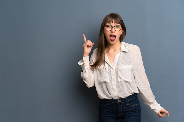 指を上向きのアイデアを考えて水色の壁の上の眼鏡を掛けた女性 Premium写真