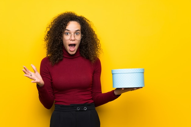 ギフト用の箱を手で押しタートルネックセーターとドミニカ人の女性 Premium写真