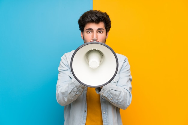メガホンを通して叫んでいるハンサムな男 Premium写真
