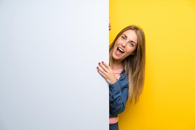 Молодая женщина держит пустой плакат, делая жест сюрприз Premium Фотографии