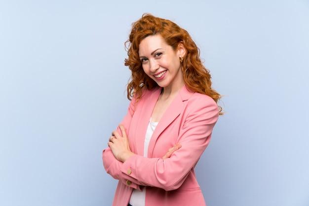 腕を組んで、楽しみにして分離の青い壁の上のスーツの赤毛の女性 Premium写真