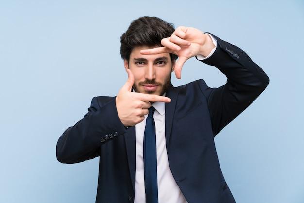顔を集中して孤立した青い壁の上の実業家。フレーミングシンボル Premium写真