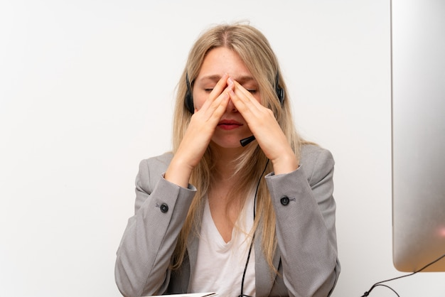 頭痛とオフィスでヘッドセットを扱う若い女性 Premium写真