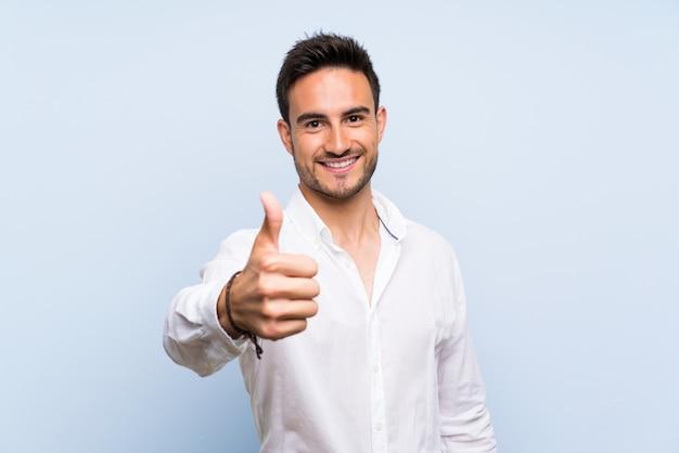 何か良いことが起こったので親指で孤立した青い上ハンサムな若い男 Premium写真