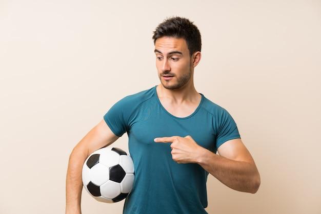 サッカーボールを保持している分離の上ハンサムなスポーツ男 Premium写真