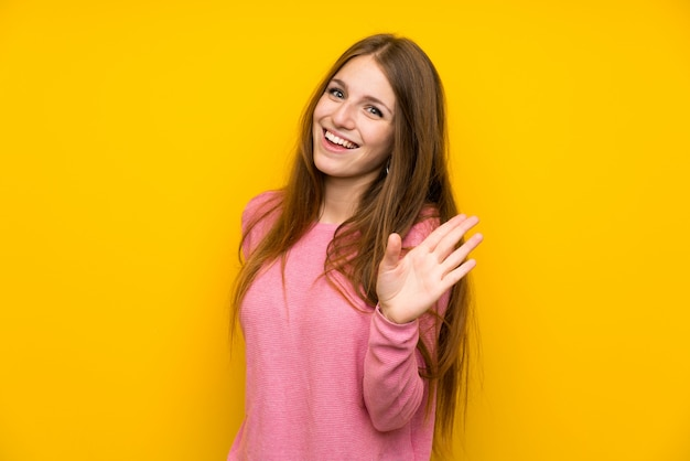幸せな表情で手で敬礼孤立した黄色の壁の上の長い髪を持つ若い女 Premium写真