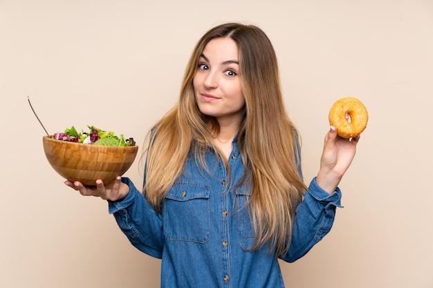 サラダとドーナツを持つ若い女 Premium写真