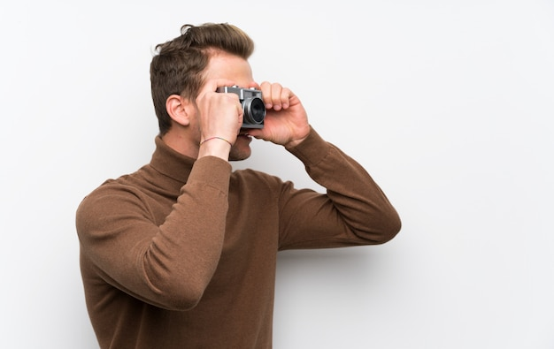 カメラを持って孤立した白い壁に金髪の男 Premium写真