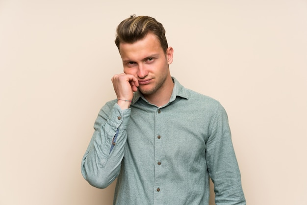 不幸な欲求不満と孤立した壁の上の金髪のハンサムな男 Premium写真