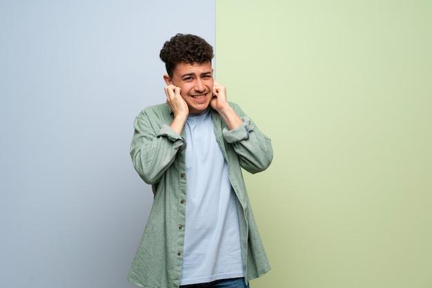 手で耳を覆っている青と緑の上の若い男。欲求不満の表現 Premium写真