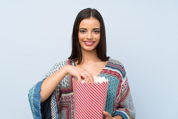 ポップコーンのボウルを保持している孤立した青い壁を越えて若い女性 Premium写真