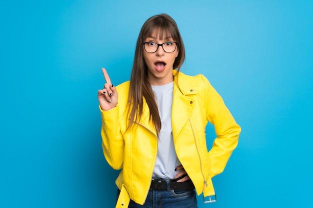 指を上向きのアイデアを考えて青に黄色のジャケットを持つ若い女 Premium写真