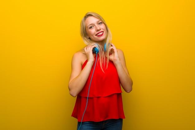 ヘッドフォンで黄色の壁を越えて赤いドレスを持つ若い女の子 Premium写真