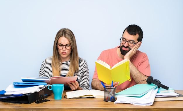 たくさんの本を持っていると強調した二人の学生 Premium写真