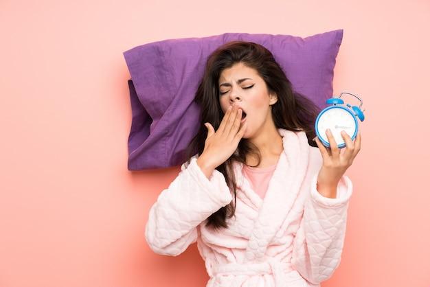 Девушка-подросток в халате на розовом фоне держит винтажные часы Premium Фотографии