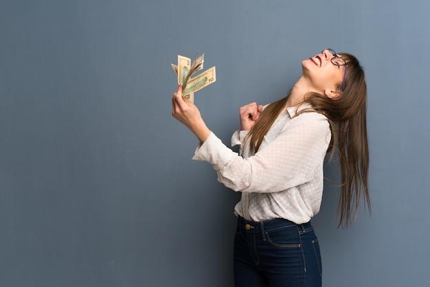 たくさんのお金を取って青い壁の上の眼鏡を掛けた女性 Premium写真
