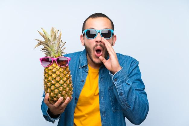コロンビア人、口を大きく開いて叫んでサングラスをかけたパイナップルを保持 Premium写真