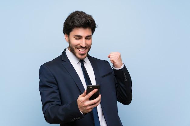 勝利の位置に携帯電話で孤立した青い壁の上の実業家 Premium写真