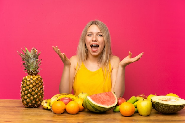 不幸なと何かにイライラした果物をたくさん持つ若いブロンドの女性 Premium写真