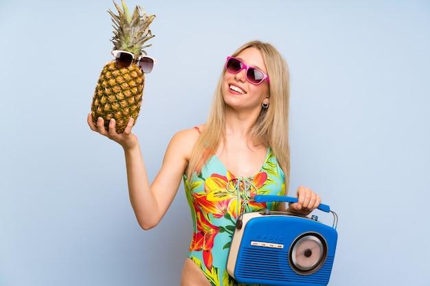 サングラスとラジオでパイナップルを保持している水着の若い女性 Premium写真