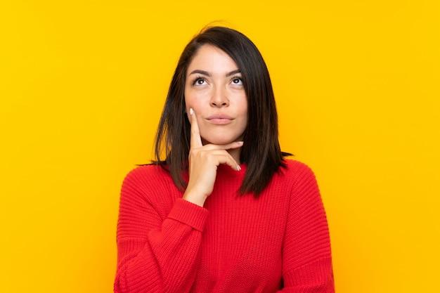 アイデアを考えて黄色の壁の上の赤いセーターを持つ若いメキシコ人女性 Premium写真