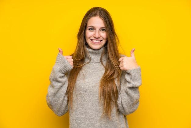ジェスチャー親指をあきらめて黄色の背景の上の長い髪を持つ若い女 Premium写真
