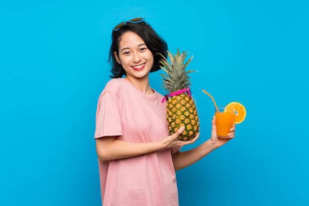 サングラスとパイナップルを保持している孤立した青い背景上のアジアの若い女性 Premium写真