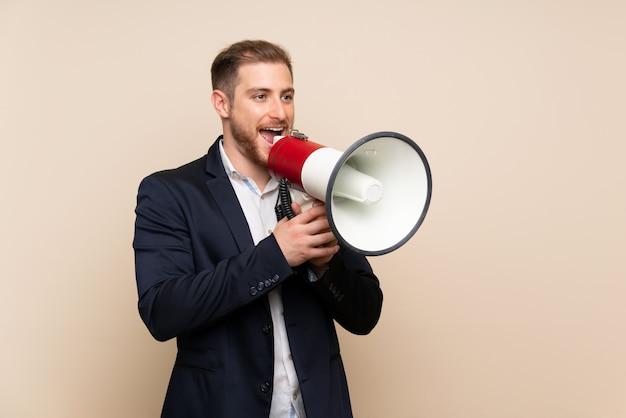 メガホンを通して叫んで孤立した背景に金髪の男 Premium写真