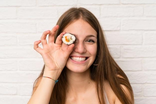 寿司を食べる長い髪を持つ若い女 Premium写真