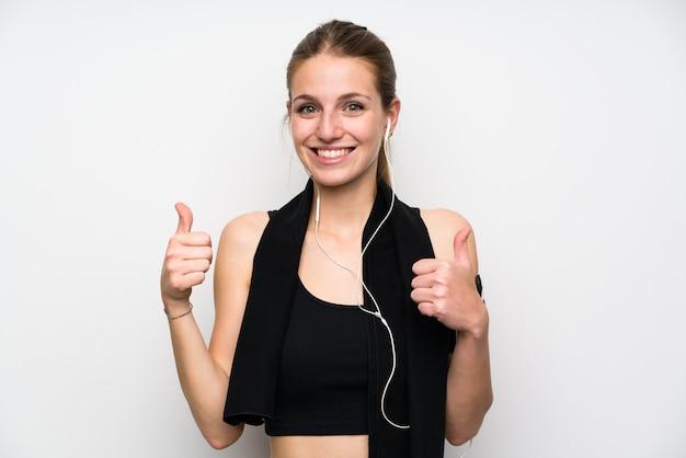 親指ジェスチャーを与える孤立した白い背景の上の若いスポーツ女性 Premium写真