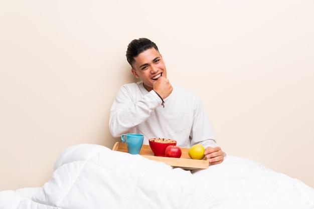 勝利を祝ってベッドで朝食を持っている若い男 Premium写真