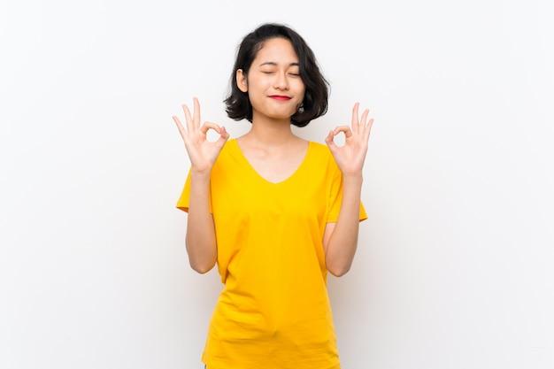 禅ポーズで孤立した白い背景の上のアジアの若い女性 Premium写真