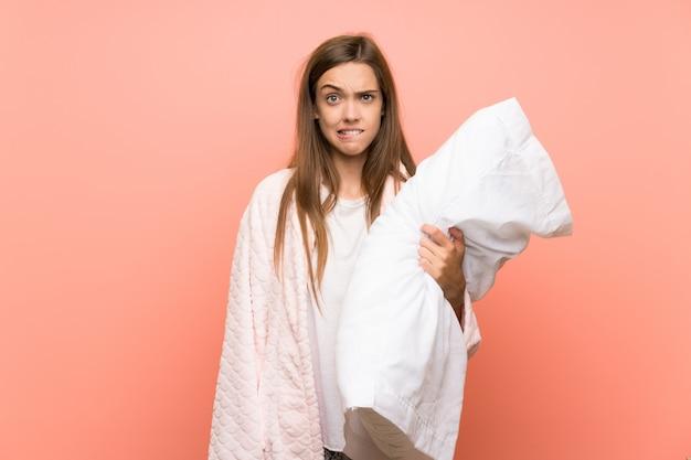 疑問を持つと混乱の表情でピンクの壁の上のドレッシングガウンの若い女性 Premium写真
