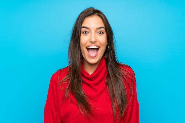 驚きの表情を持つ赤いセーターを持つ若い女 Premium写真