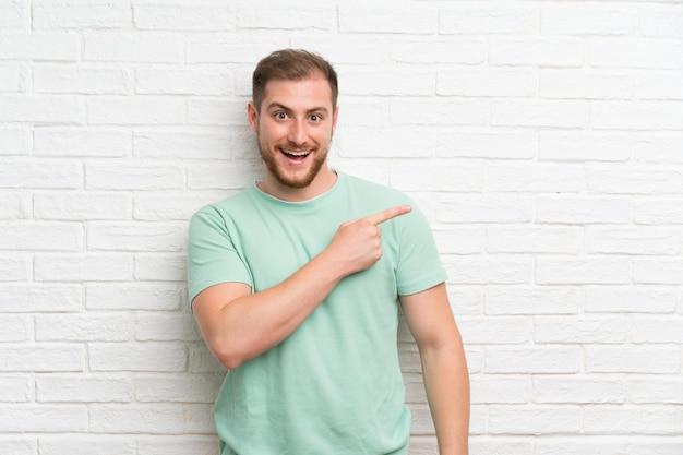 側に指を指しているレンガの壁を越えて金髪の男 Premium写真