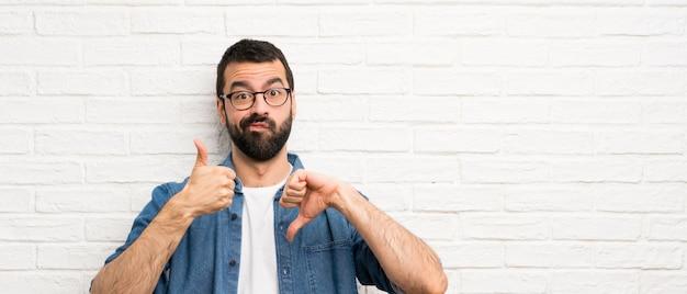悪いサインを作る白いレンガの壁の上のひげを持つハンサムな男。はいかどうかは未定 Premium写真