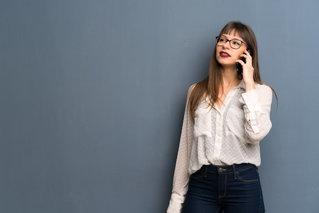 携帯電話との会話を維持するメガネの女 Premium写真