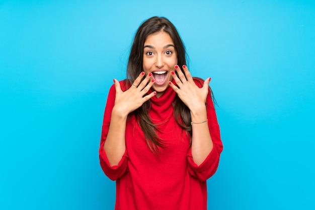 驚きの表情で分離された青の赤いセーターを持つ若い女 Premium写真
