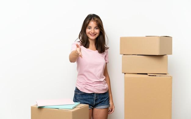 かなりの後のハンドシェイクボックス間で新しい家に移動する若い女の子 Premium写真