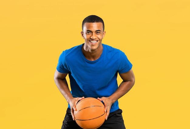 黄色に分離されたアフロアメリカンバスケットボール選手男 Premium写真
