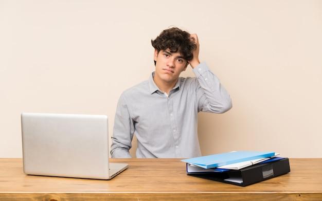 欲求不満の表現と理解していないラップトップを持つ若い学生男 Premium写真