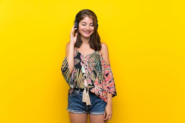 ヘッドフォンで音楽を聞いて孤立した黄色の背景にカラフルなドレスの白人少女 Premium写真