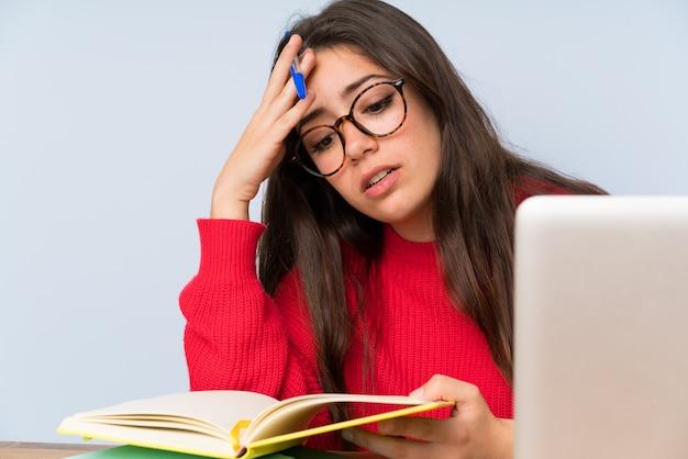 テーブルで勉強して欲求不満のティーンエイジャー学生少女 Premium写真