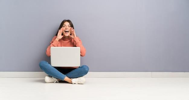 口を大きく開けて叫んで床にラップトップを持つ若い学生の女の子 Premium写真