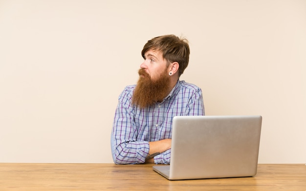 側を見ているラップトップを持つテーブルで長いひげを持つ赤毛の男 Premium写真
