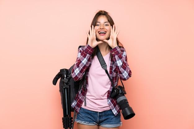 口を大きく開けて叫んでいる若い写真家の女の子 Premium写真