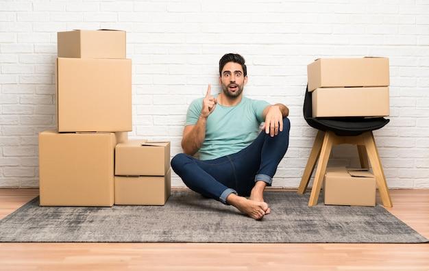 ハンサムな若い男の人差し指で指しているボックスの間で新しい家に移動する素晴らしいアイデア Premium写真