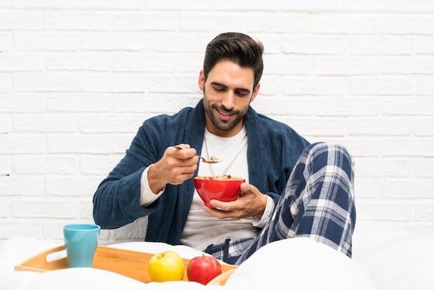 ドレッシングガウンと朝食のベッドで男 Premium写真